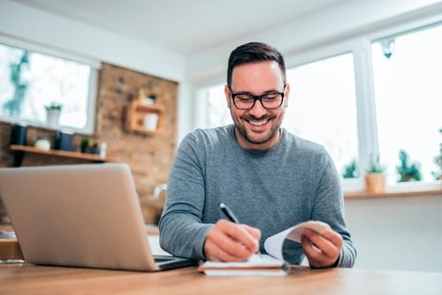 hombre con ordenador tomando apuntes en libreta