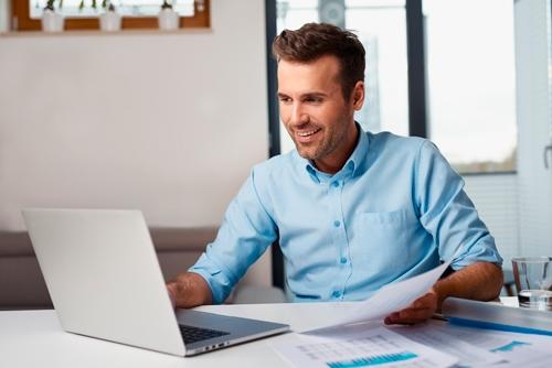 hombre alegre comparando notas en ordenador