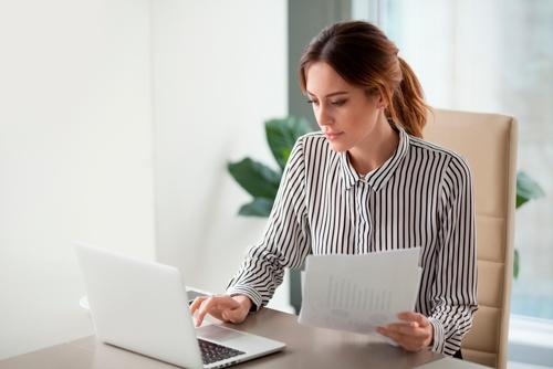 mujer en oficina con documentos y ordenador